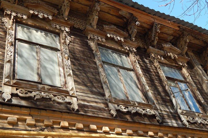 Соседний дом с традиционно деревянным верхом и каменным низом.