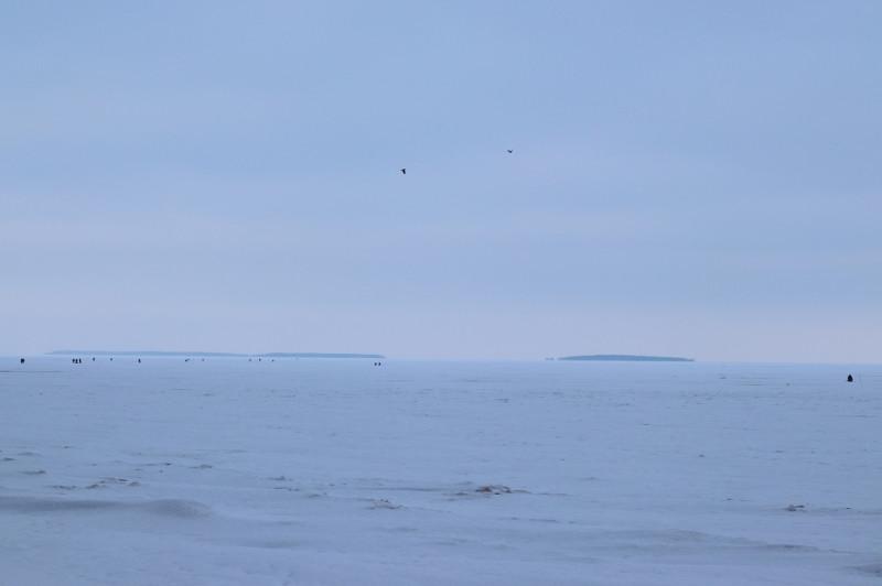 Над рыбаками кружили два ворона (чёрные точки в небе)