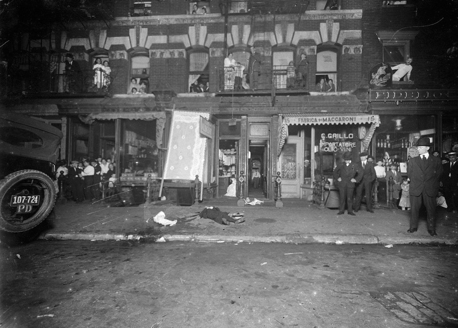 New York City Police. Crime scene with onlookers leaning out of tenement windows, a man's body on the sidewalk in front of laundry and Italian pasta makers and oil and wine importers
