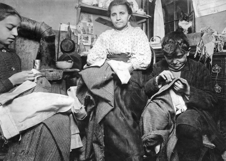 Lewis Hine - High up on the top floor of a rickety tenement, this mother and her two children were living in a tiny one room, and were finishing garments, 1912