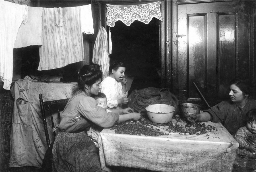Lewis Hine - Mrs. Mary Rena, picking nuts with dirty baby in lap. Two neighbors helping. Girl is cracking nuts with her teeth, not an uncommon sight. .