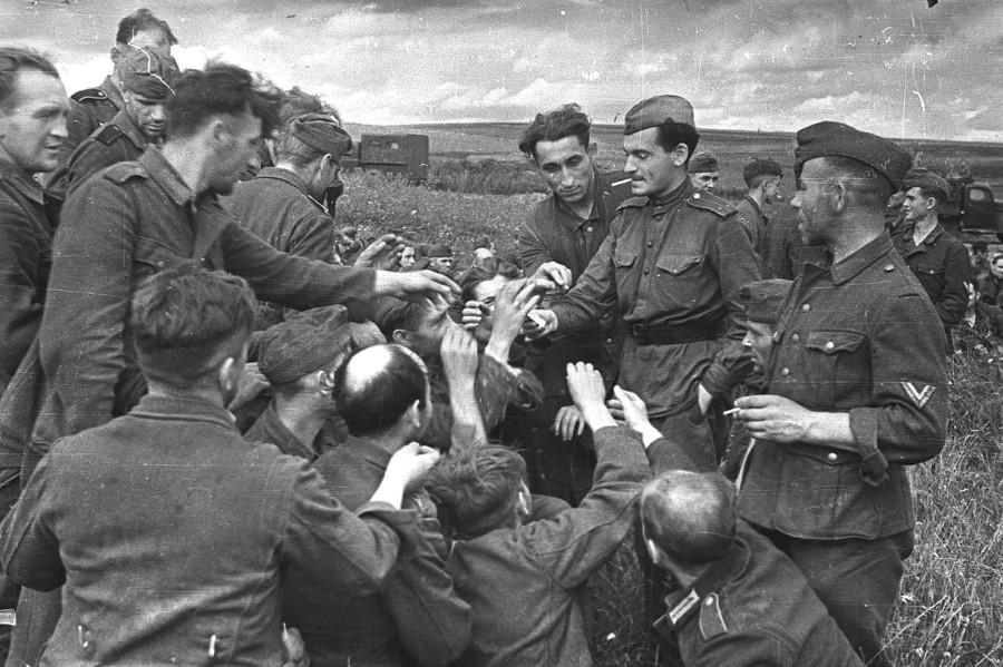 Soviet lieutenant hands cigarettes to German prisoners Kursk, July 1943.