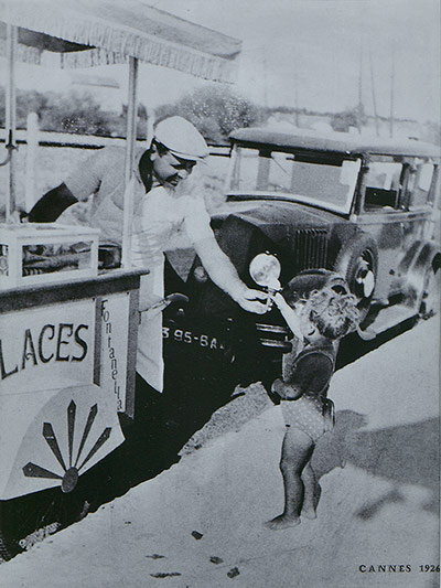 4_A gelatiere hands a cone to a child in Cannes France 1926