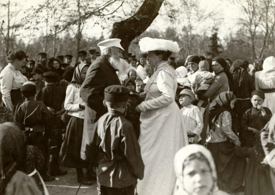Лев и Софья Толстые и их дочь Александра среди крестьян деревни Ясная Поляна в Троицын день 1909 г. Т. Тапсель