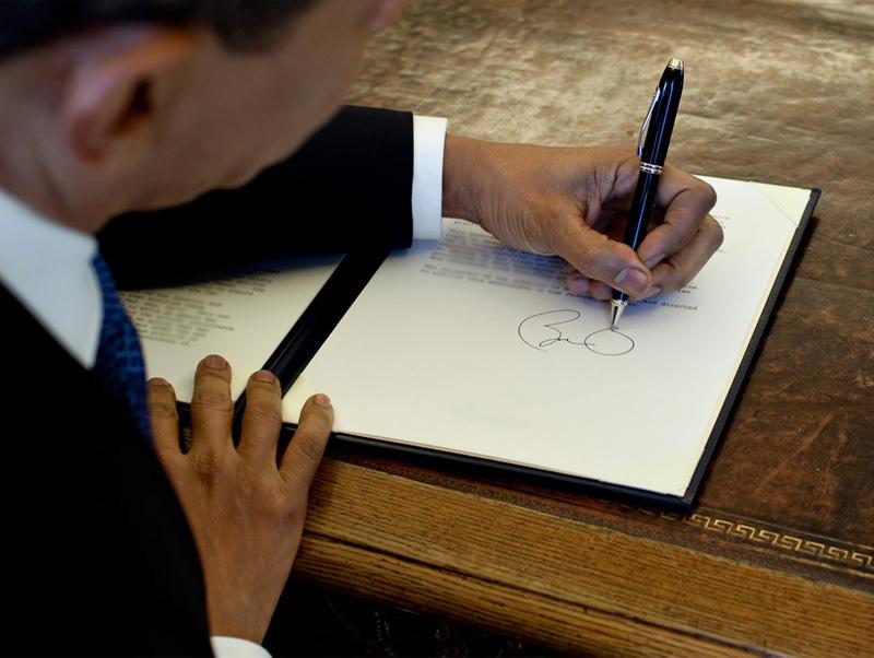 Obama-signs-at-his-desk