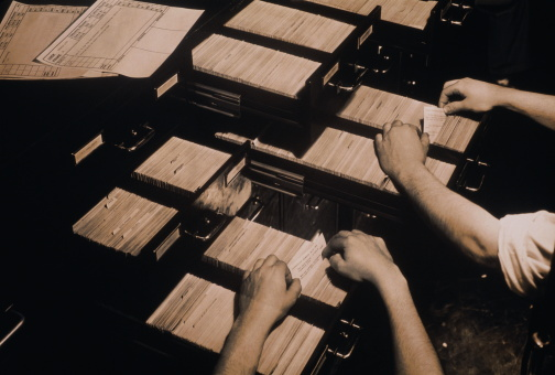 Hands filing cards