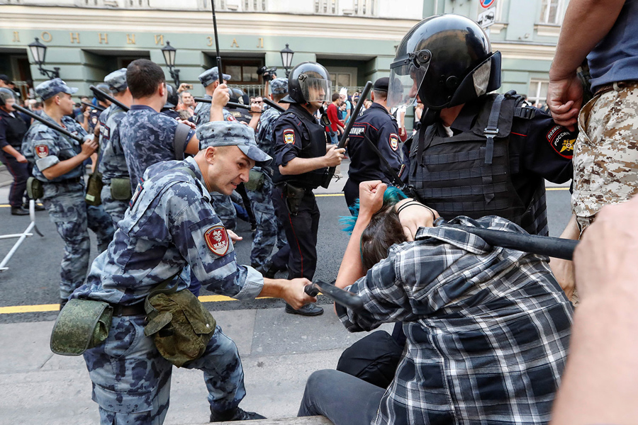 A serviceman of the Russian National Guard beats a protester