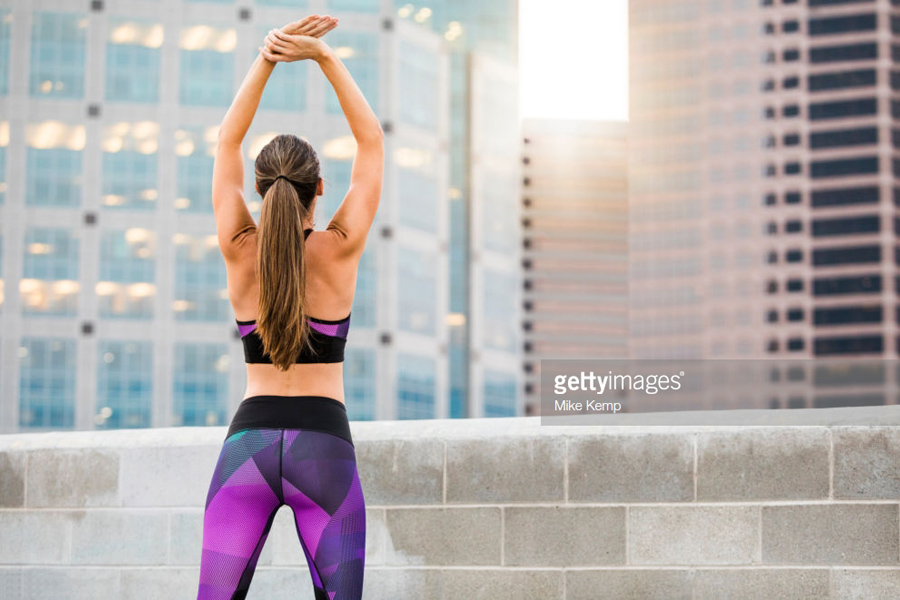 Woman Stretching On Urban Rooftop