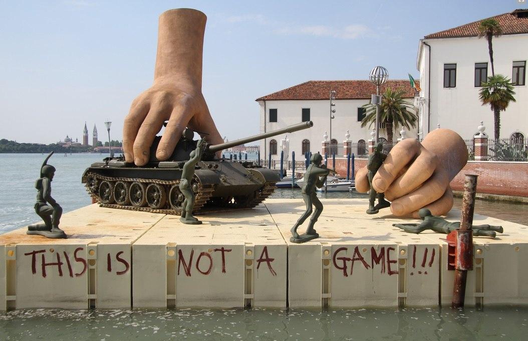 Скульптура большие руки играют солдатами и танком
