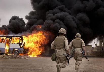 GIs runing near burning bus