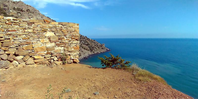 Угол восточной стены загораживает начало тропы по Караул-Обе, там находится рукотворная каменная кладка, просевшая под весом ползущего вниз склона горы. От мыса, выходящего в море, начинается Боспорская бухта.
