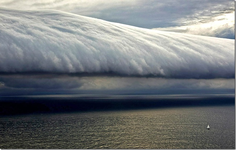 This handout photo taken and released on December 27, 2010 by Rolex shows a competitor (lower R) heading towards a storm front near the Bass Strait during the 66th Sydney Hobart Yacht Race. Thunderstorms and hail hit the Sydney to Hobart fleet overnight, with two men thrown into the swell at one point, but only one boat has so far withdrawn from the ocean race, organisers said on December 27, 2010.