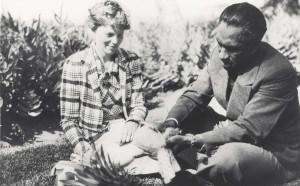 Honolulu Sheriff Duke Kahanamoku shows Amelia Earhart how pineapples are prepared for eating, January 2, 1935 at the Royal Hawaiian Hotel