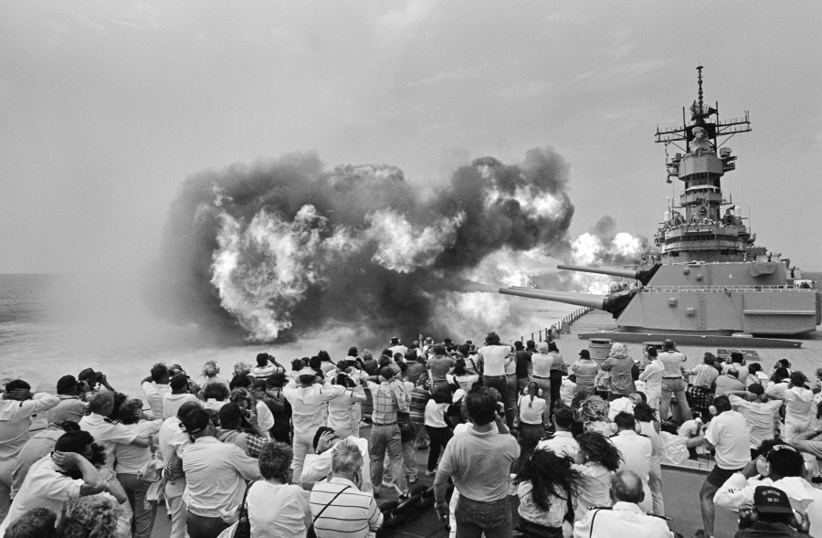 Guests attending a Dependents Day Cruise aboard the battleship USS MISSOURI (BB 63) cover their ears as the ship fires its Mark 7 16-inch 50-caliber guns during a firepower demonstration, 08-24-1988 a