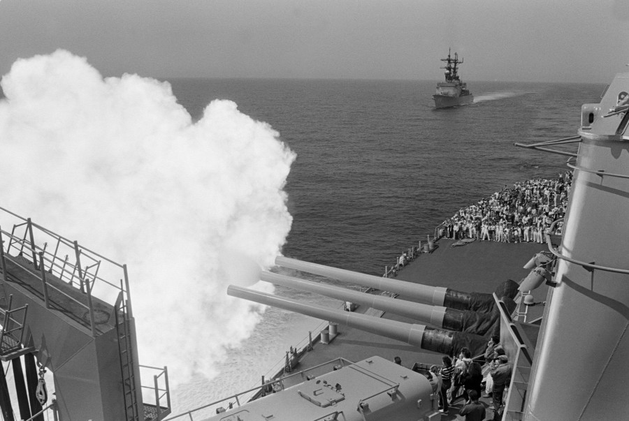 Guests attending a Dependents Day Cruise aboard the battleship USS MISSOURI (BB 63) cover their ears as the ship fires its Mark 7 16-inch 50-caliber guns  08-24-1988 USS MERRILL (DD 976) behind