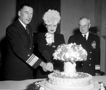 Vice Admiral Blandy and his wife cut the cake celebrating Operation Crossroads as Rear Admiral Frank J. Lowry looks on.