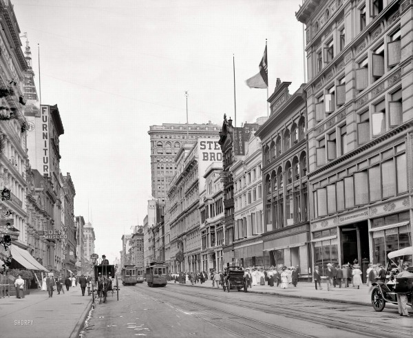 New York circa 1908. West 23rd Street from Sixth Avenue. Two landmark skyscrapers on view -- the Flatiron Building at right and Metropolitan Life tower going up at left