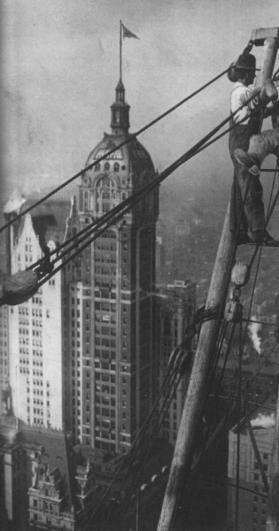 Worker on crane during the construction of Bankers Trust Building. October 1911. The Singer Building show here on background