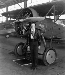Amelia Earhart with airplane, in hangar, July 30, 1936