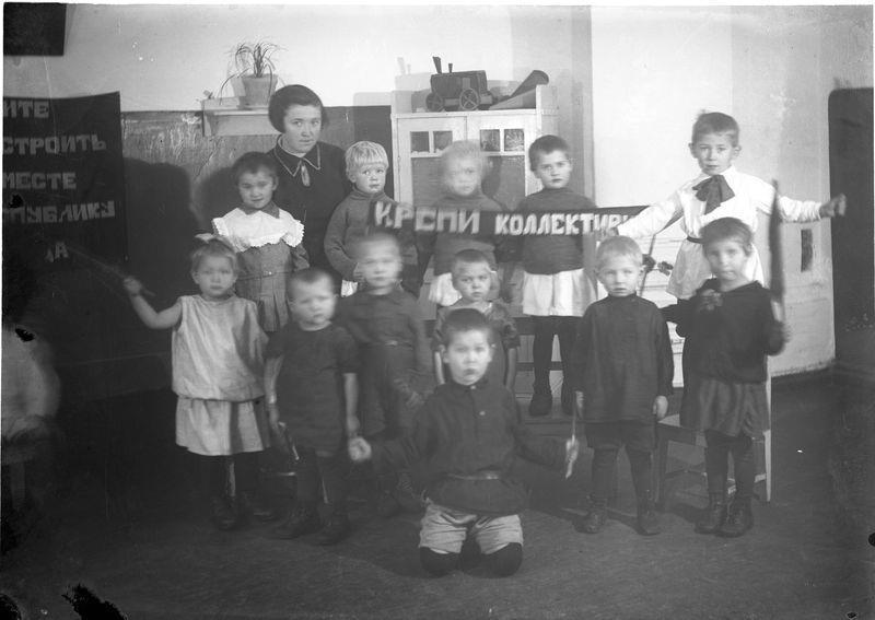 Группа детсадовцев с лозунгом Крепи коллектив!