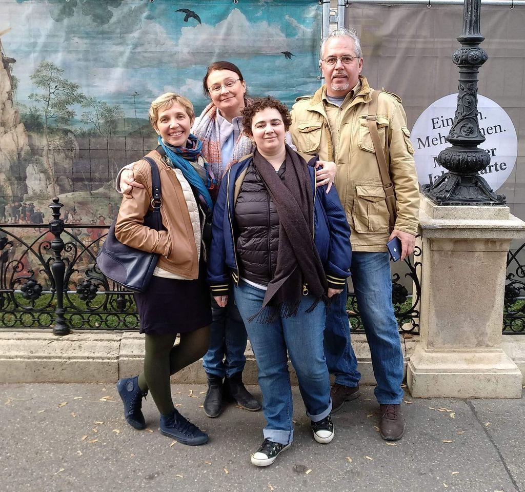 Оля Х., Оля У., Юля Ф. и Саша У. на фоне баннера про выставку Брейгеля у Музея истории искусств, Вена