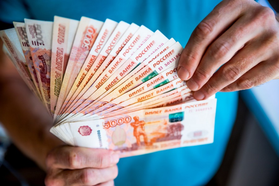 man-fanning-a-stack-of-russian-ruble-banknotes