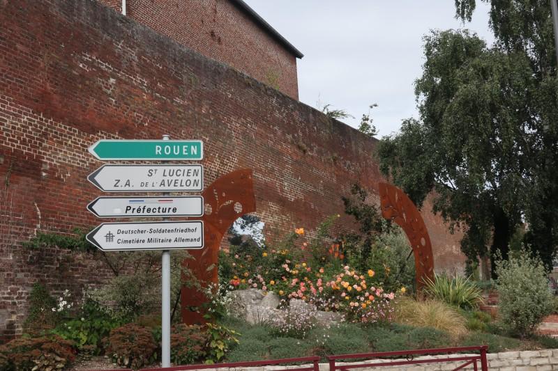 25. Клумба у тюремной стены. Указатель на кладбище немецких солдат, находящееся неподалеку.