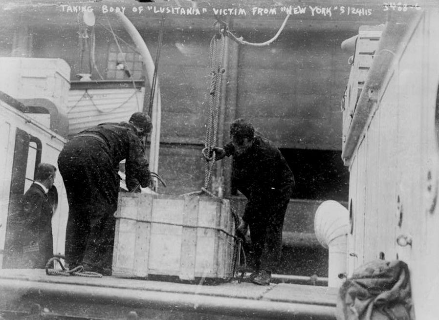 Жертвы Лузитании. Двое мужчин достают ящики с телами жертв из спасательного судна.