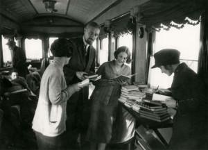 Вагон-библиотека, где во время пути можно почитать книги и журналы.Люди стоял в комнате с книгами в руках. Работница железнодорожной библиотеки что-то отмечает у себя в книге.