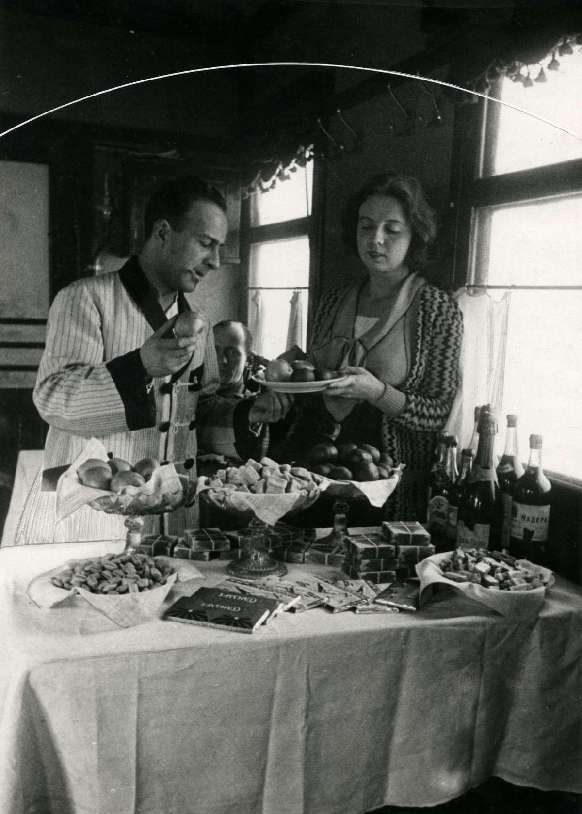 Вагон-ресторан, предлагающий лучшие блюда русской кухни. Мужчина и женщина стоят возле стола с фруктами, шоколадом и бутылками и вина.