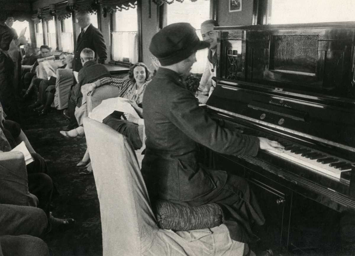 Во время долгого путешествия поездом пассажиров развлекают музыкальными выступлениями. Железнодорожница играет на фортепиано.