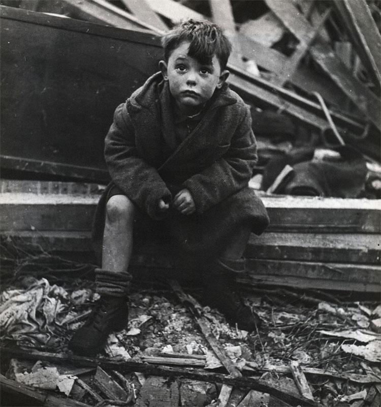 Мальчик сидит в развалинах своего дома, где его родители похоронены под обломками после взрыва Фау-2. Лондон, январь 1945