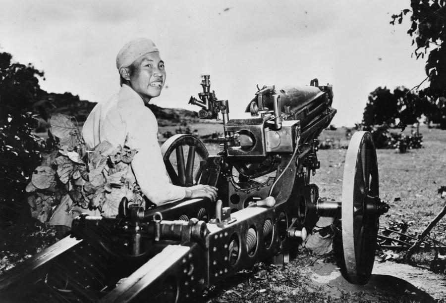 Китайский артиллерист сидит возле 75-мм гаубицы М1