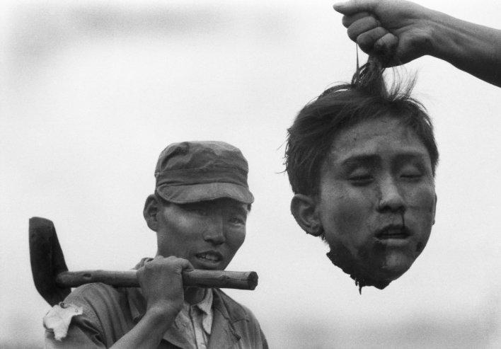 Южнокорейский полицейский держит отрубленную голову северокорейского партизана 1952