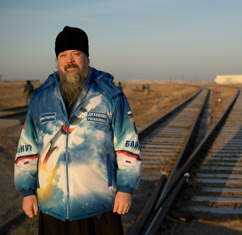 Russian Orthodox Priest Father Sergei poses for a photograph as he waits for the train transporting the Soyuz rocket to the launch pad to pass, Tuesday, March 12, 2019 at the Baikonur Cosmodrome in Kazakhstan