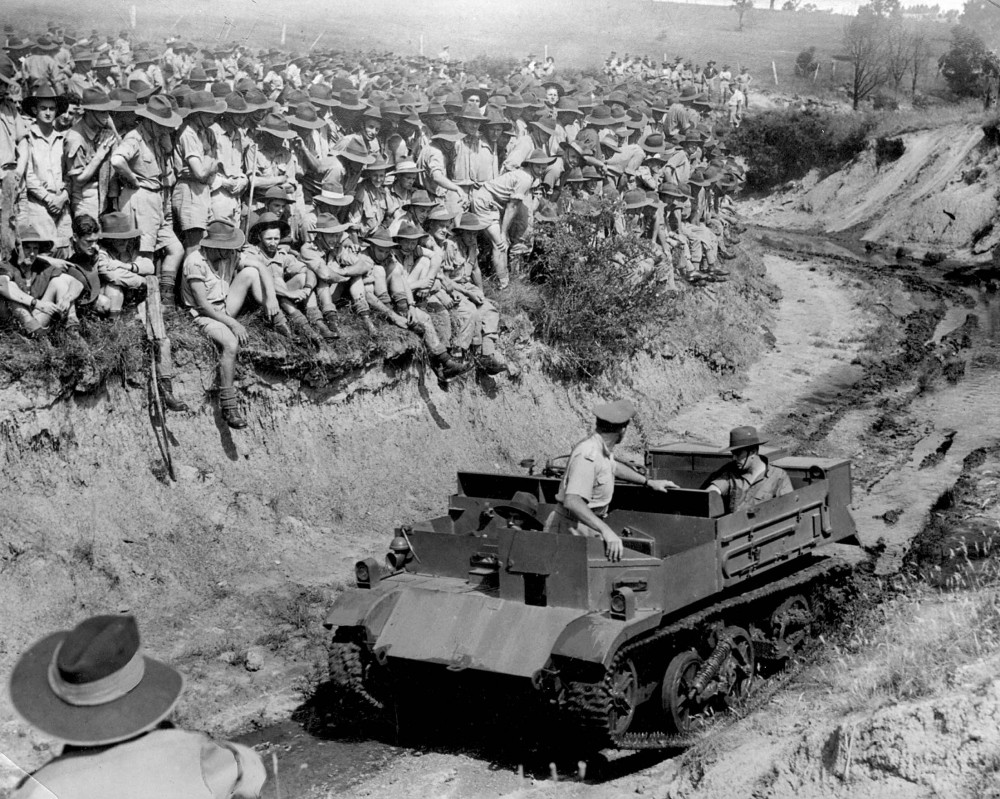 Troops on manoeuvres [ca. 1942] Large group of soldiers assembled near a wide ditch, tank being driven along ditch