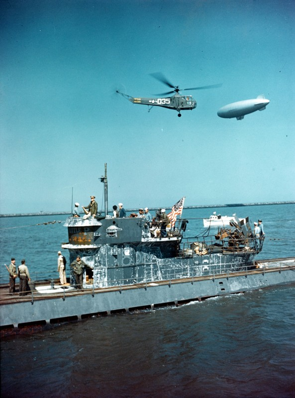 The German submarine U-858 arrives in port after surrendering to American forces off the coast of Delaware in May, 1945. K class blimp monitoring the sub as well as a Sikorski HNS-1 helicopter