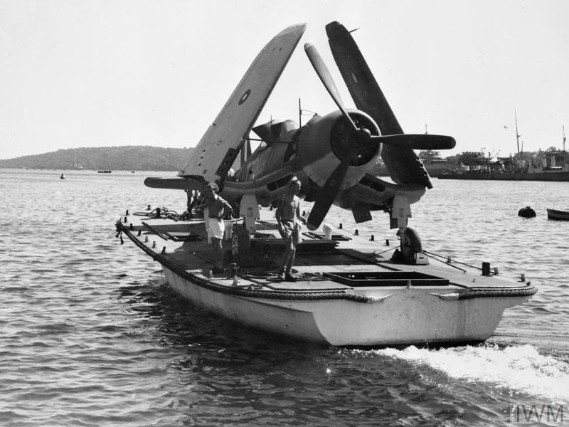 An F4U Corsair of the Fleet Air Arm is transported back to its carrier after being repaired at a shore-based facility in Colombo, Ceylon ( now Sri Lanka) April 194