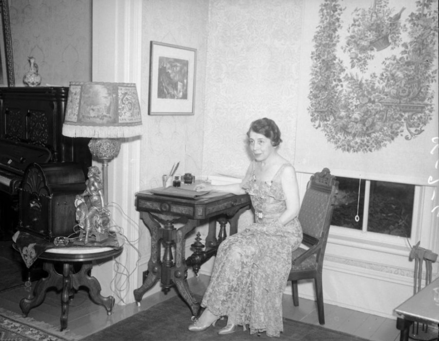 View of a woman in a brocade dress sitting at a desk, in (possibly) Bay Doe's suite at the Hotel Windsor, in Denver, Colorado. July 6, 1935