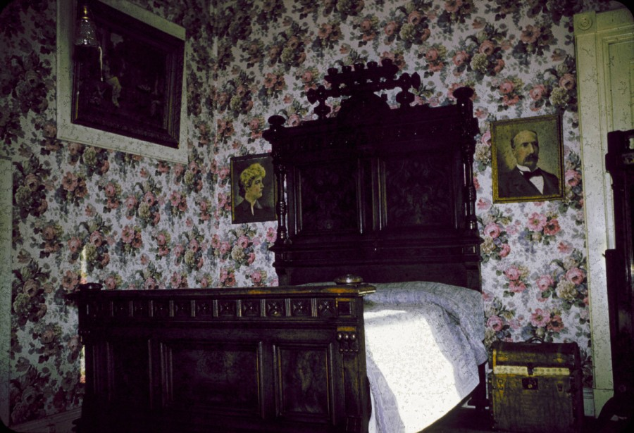 Interior view of the bedroom in the Tabor suite at the Windsor Hotel at 18th (Eighteenth) and Larimer Streets in Denver, Colorado. A bed, nightstand, and portraits of the Tabors are in the room [1955]