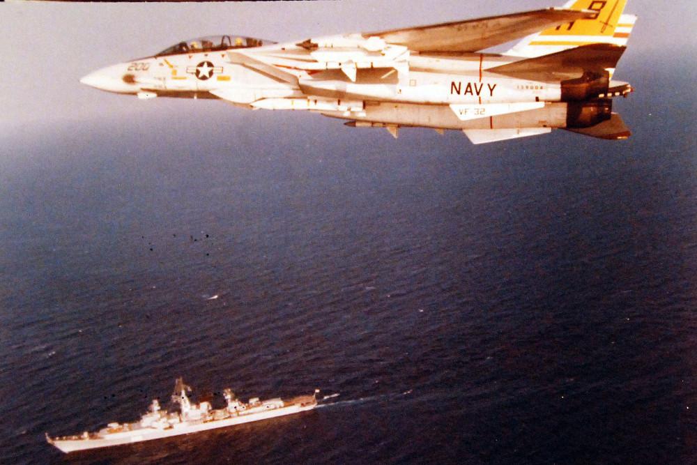 Mediterranean Sea. A Fighter Squadron 32 (VF 32), F-14A Tomcat  in flight near a Soviet Kresta II class guided missile cruiser underway below. January 1976