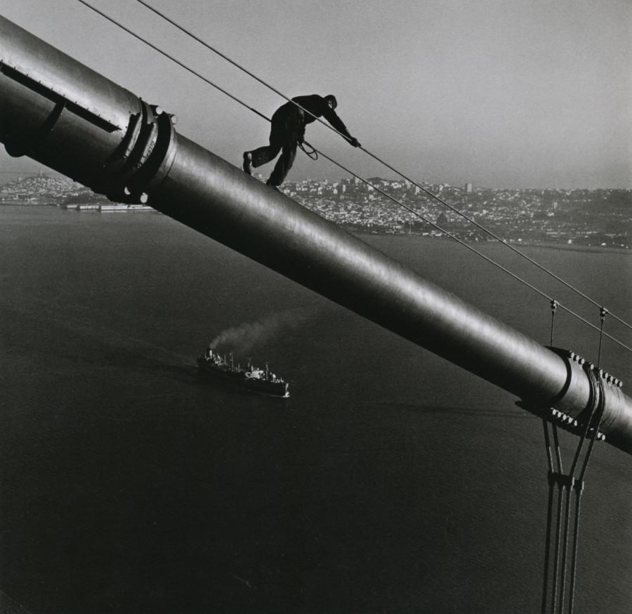 A maintenance worker walks down the cables of San Francisco's Golden Gate Bridge (1947)