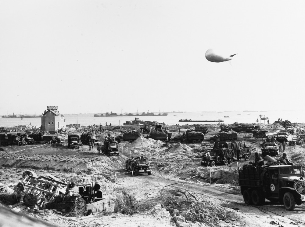 U.S. Army trucks move inland from Omaha Beach, soon after the landings there. Note USS LCT-305 on the beach in center, with a Rhino just offshore to the right