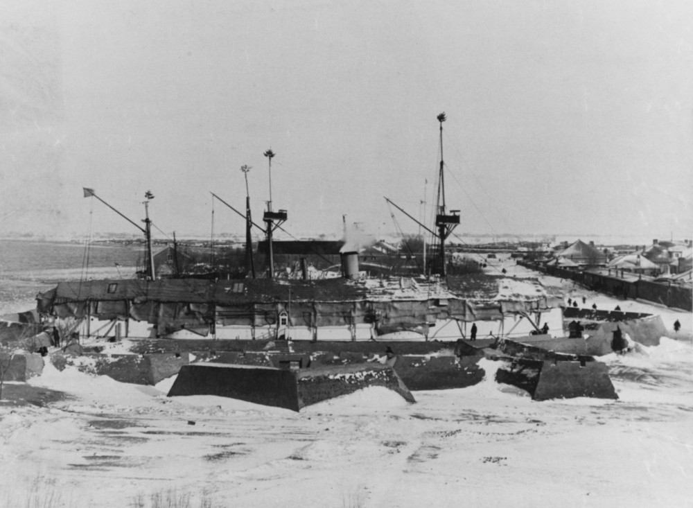 USS Petrel (PG-2) laid up for the winter, inside the mud fort at Miuchwang, China during the 1890s. Photographed on Christmas Day, Christmas trees at mast tops. Masts of British gunboat HMS Firebrand are in the background.