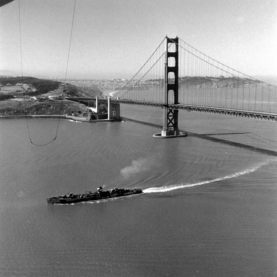 The damaged Fletcher-Class Destroyer USS Hazelwood DD-531 passes under the Golden Gate Bridge on her way to Mare Island Naval Shipyard for repairs - June 1945