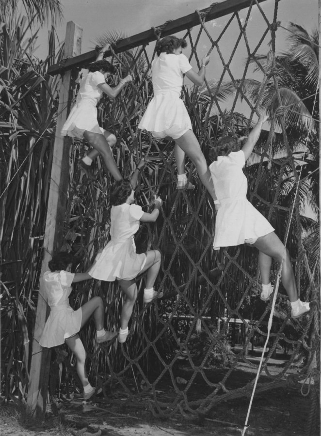Navy Women Accepted for Volunteer Emergency Service (WAVES) climb a cargo net during training in Miami, Florida, 1944