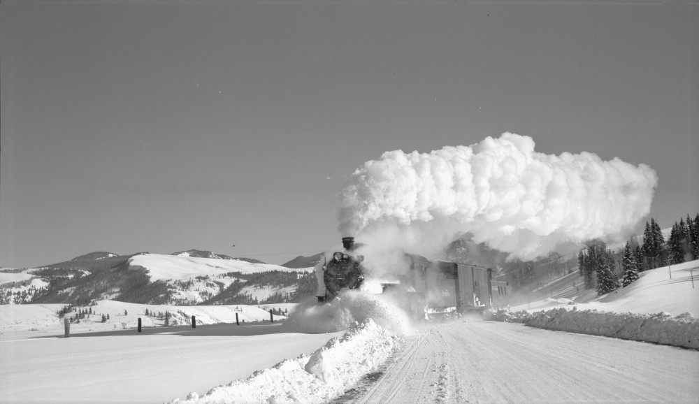 D&RGW locomotive #1177 (2-8-0), with a boxcar and caboose, plows through snow between Wagon Wheel Gap and Wason (Mineral County), Colorado. 1949 January 18