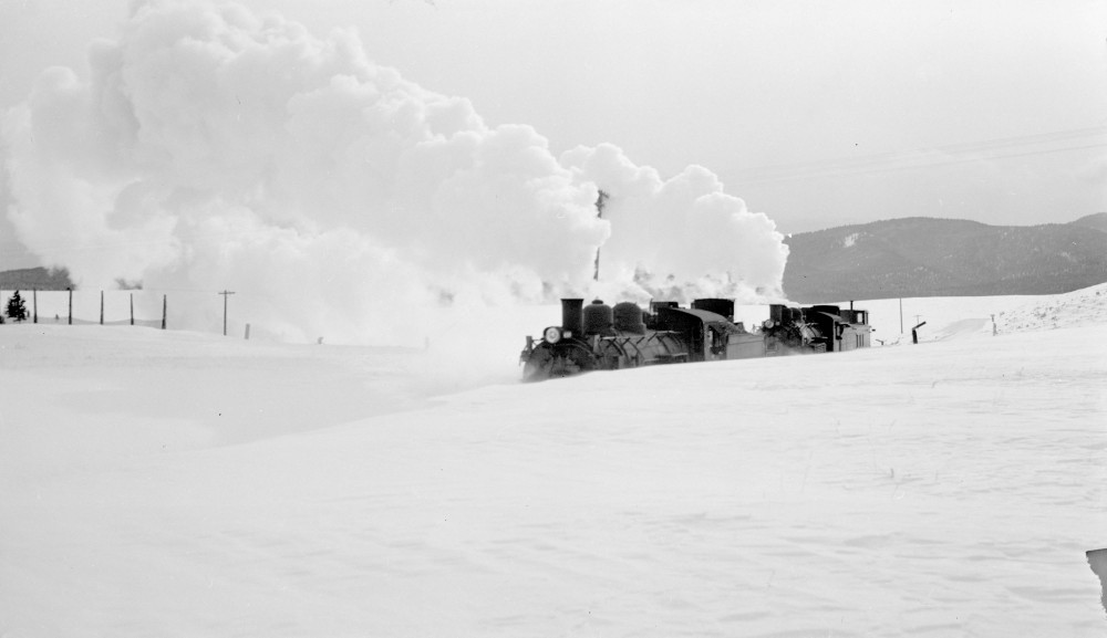 Two Denver and Rio Grande Western locomotives in deep snow on the Poncha Pass road in Chaffee County, Colorado. Locomotive 496 vents steam. 1949 January 28