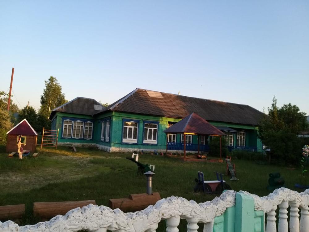 На красивым бетонным забором находится деревянное здание детского сада