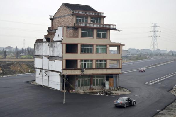 Новая дорога в провинции Чжэцзян, Китай. Пожилая пара, проживающая в этом доме, отказалась подписывать соглашение на снос дома из-за слишком низкой, по их мнению, компенсации.